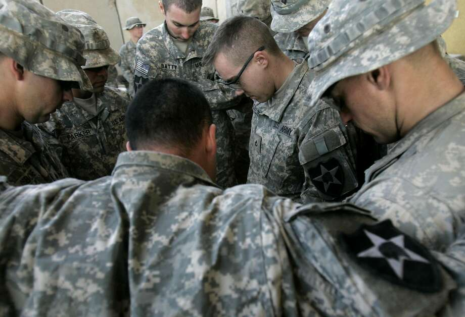 U.S. army soldiers from Blackfoot Company, 2nd Battalion, pray before Christmas lunch in Iraq in 2007. Photo: Marko Drobnjakovic / Associated Press 2007
