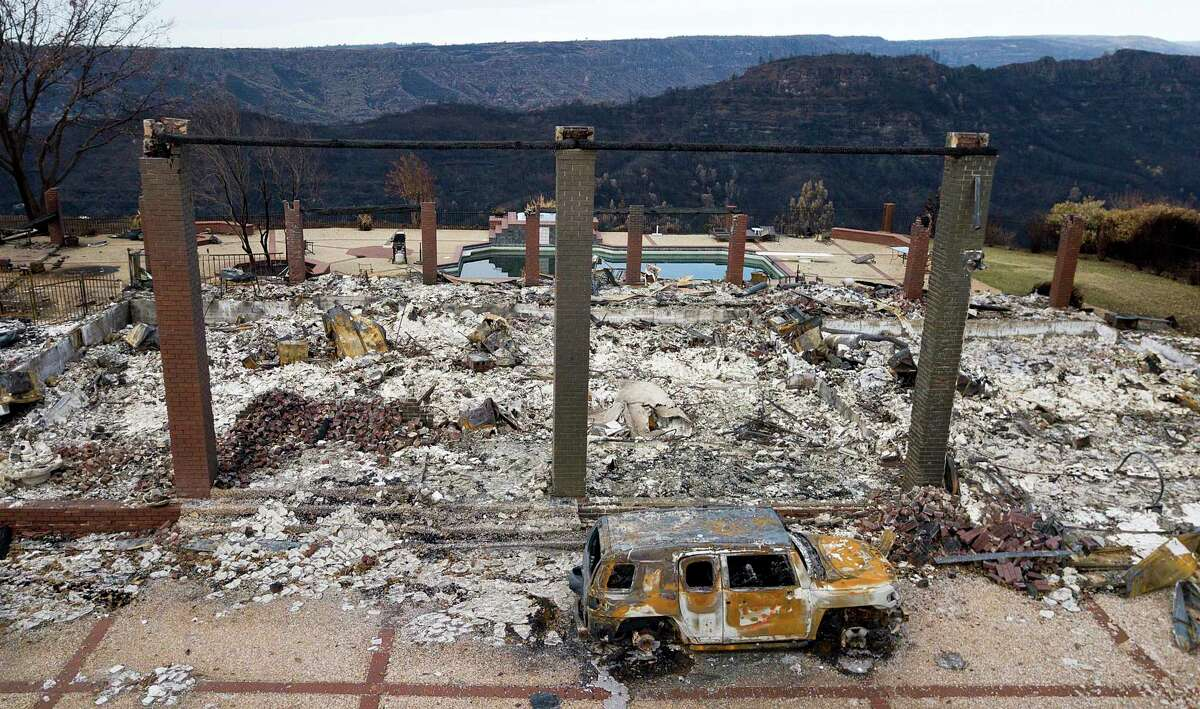 In this Dec. 3, 2018 file photo, a vehicle rests in front of a home leveled by the Camp Fire in Paradise, Calif. Authorities estimate it will cost at least $3 billion to clear debris of 19,000 homes destroyed by California wildfires last month. State and federal disaster relief officials said Tuesday, Dec. 11, 2018, that private contractors will most likely begin removing debris in January from Butte, Ventura and Los Angeles counties and costs are likely to surpass initial estimates. (AP Photo/Noah Berger, File)