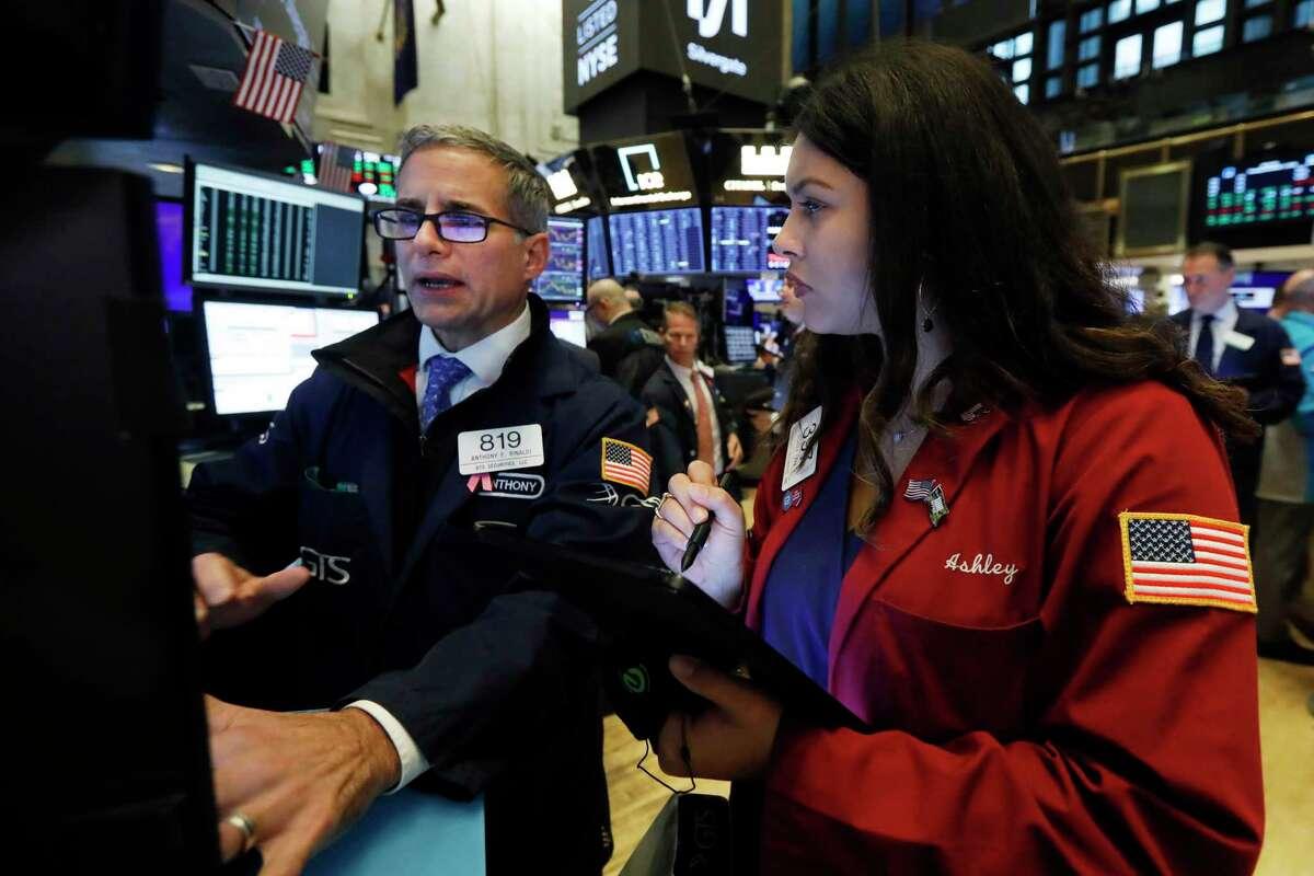 Specialist Anthony Rinaldi, left, and trader Ashley Lara work on the floor of the New York Stock Exchange, Thursday, Nov. 7, 2019. (AP Photo/Richard Drew)