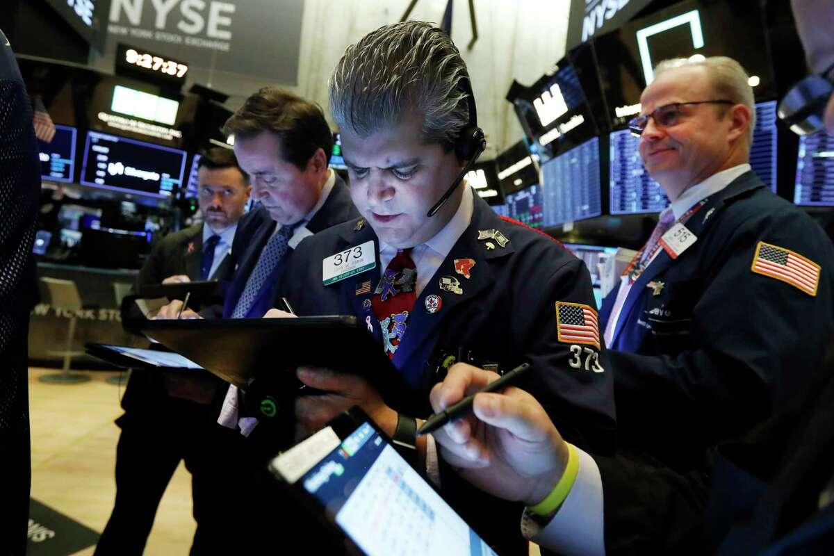 John Panin, center, works with fellow traders on the floor of the New York Stock Exchange, Thursday, Nov. 7, 2019. (AP Photo/Richard Drew)