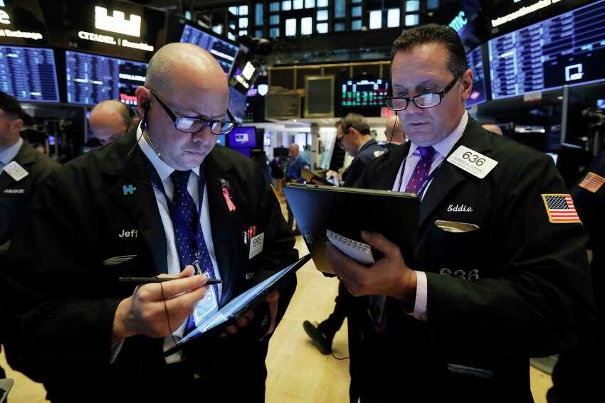 Traders Jeffrey Vazquez, left, and Edward Curran work on the floor of the New York Stock Exchange, Thursday, Nov. 7, 2019. (AP Photo/Richard Drew)