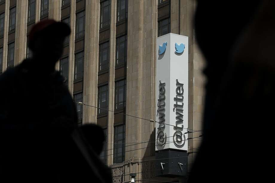 This July 9, 2019, file photo shows pedestrians walking across the street from the Twitter office building in San Francisco. Photo: Jeff Chiu / Associated Press
