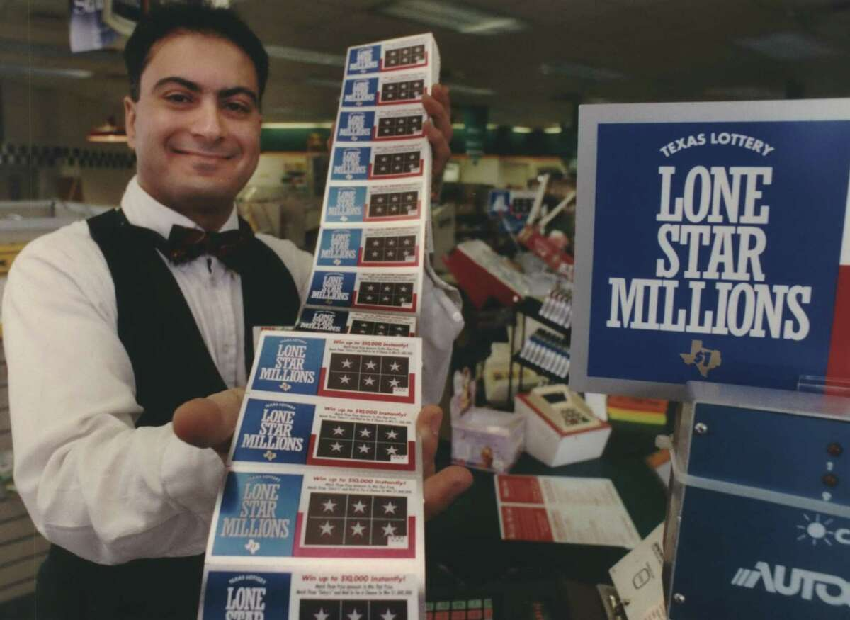 In this 1992 press photo, Raffoul Ragi with the Texas Lottery shows off scratch tickets at a Houston convenience store.
