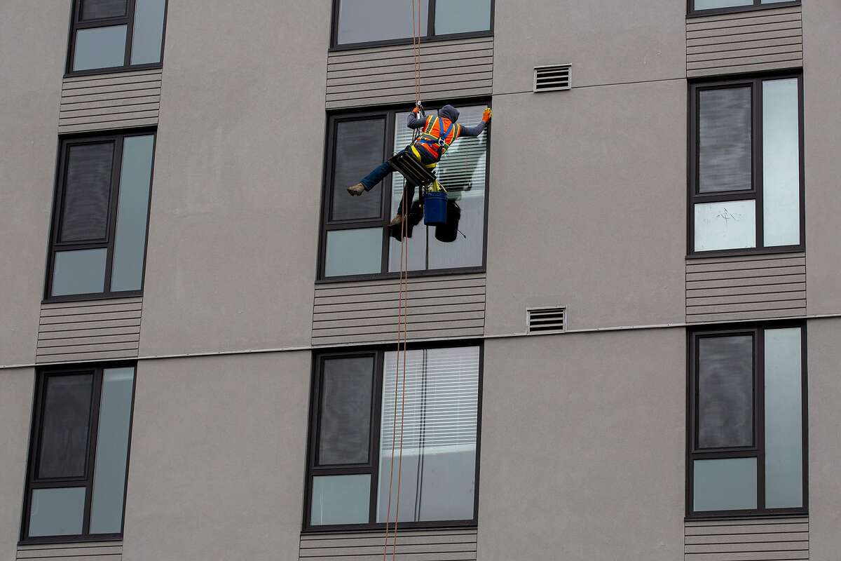 A construction worker cleans the exterior windows of the MacArthur Commons construction site on Monday, July 8, 2019, in Oakland, Calif.