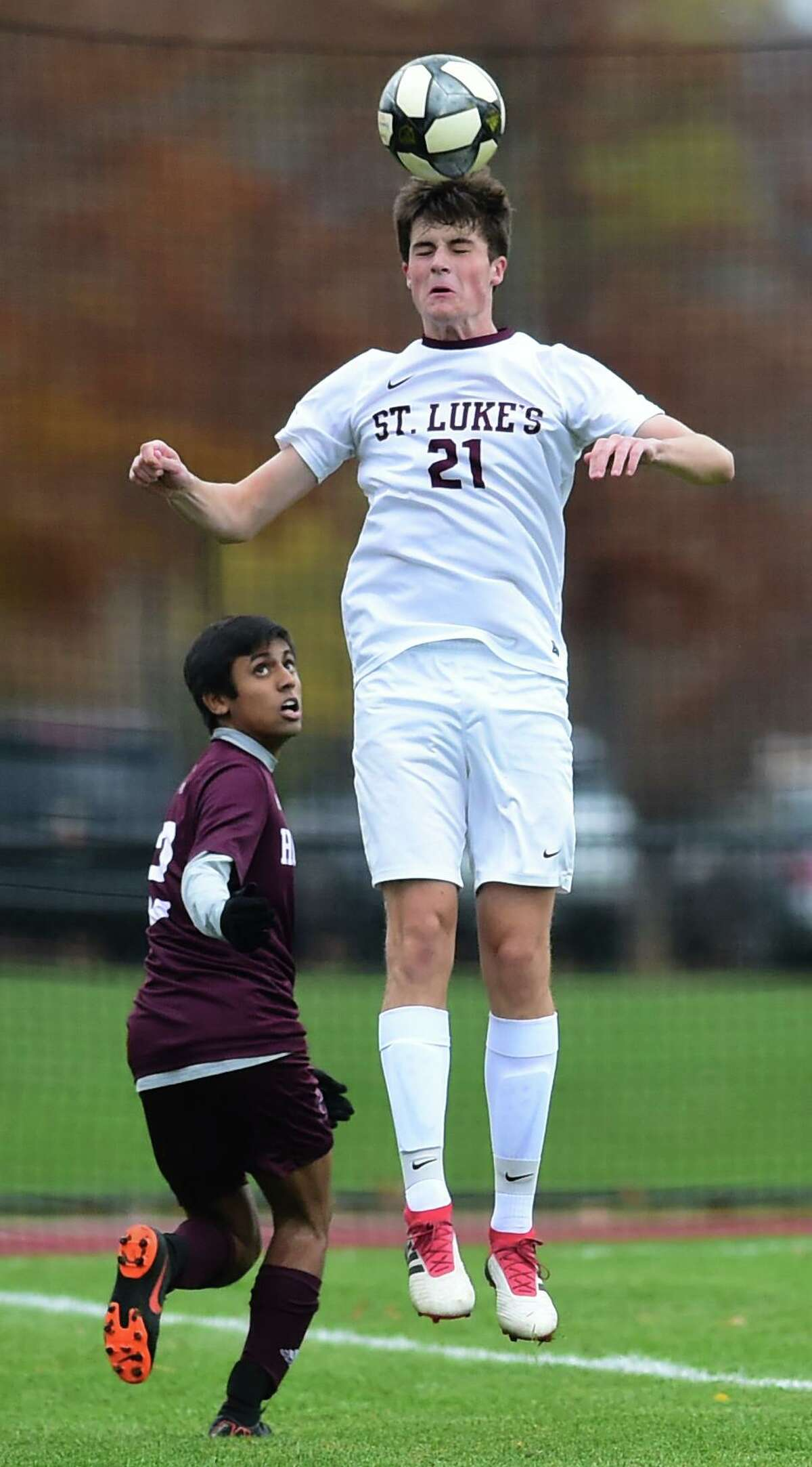 Hopkins' Suraz Kalaria, left, watches as St. Luke's Fritz Laibe heads the ball during the first half of the Fairchester Athletic Association Championship game on Thursday in New Haven.