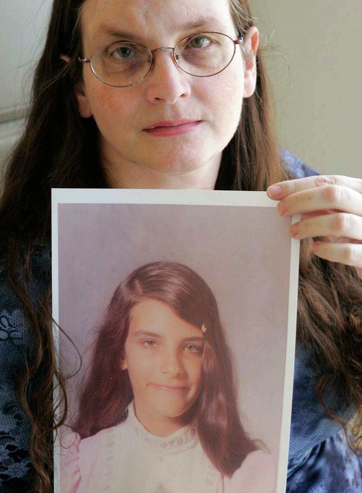 Debbie Vasquez holds a photographer of herself at age 14. Vasquez says she was raped by a Southern Baptist pastor as a teenager. (AP Photo/Donna McWilliam)