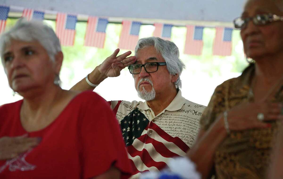 Luz Gallegos, 73, center, salutes the flag during a ceremony honoring military veterans at the Good Samaritan Center on the West Side on Thursday.