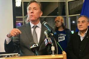 Gov. Ned Lamont presented his updated transportation plan at the offices of reSET, a business incubator in Hartford, on Nov. 7. At center is Hilary Gunn, an anti-tolls protester from Greenwich and at right is Sal Luciano, president of the Connecticut AFL-CIO, a tolls supporter.