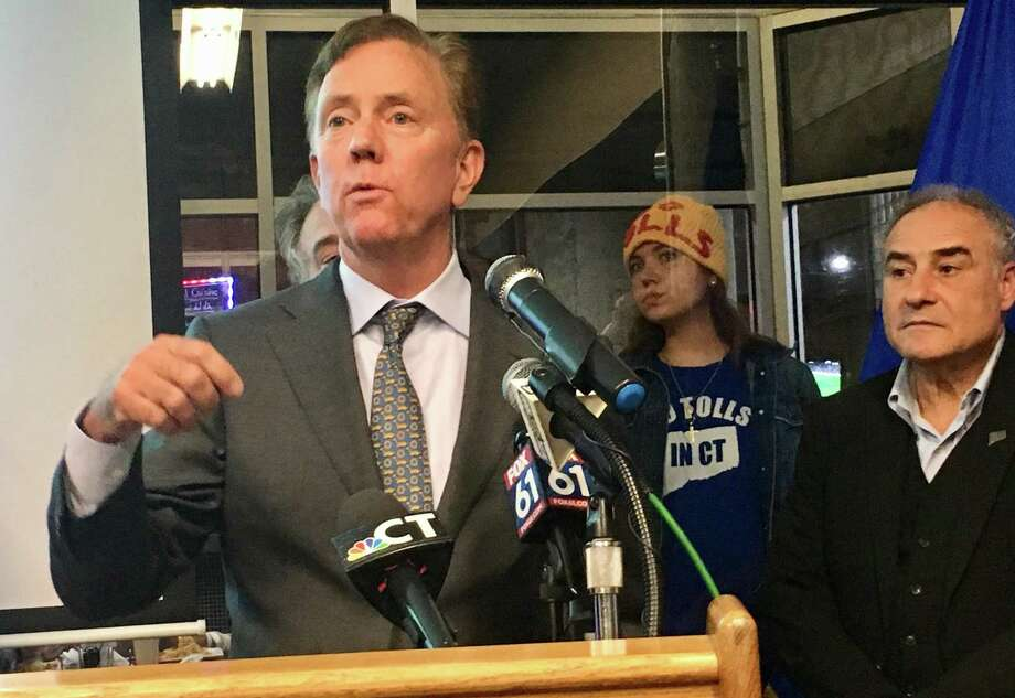 Gov. Ned Lamont presented his updated transportation plan at the offices of reSET, a business incubator in Hartford, on Thursday, Nov. 7, 2019. At center is Hilary Gunn, an anti-tolls protester from Greenwich and at right is Sal Luciano, president of the Connecticut AFL-CIO, a tolls supporter. Photo: Dan Haar/Hearst Connecticut Media