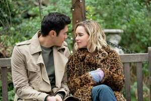 """This image released by Universal Pictures shows Emilia Clarke, right, and Henry Golding in a scene from """"Last Christmas."""" (Jonathan Prime/Universal Pictures via AP)"""