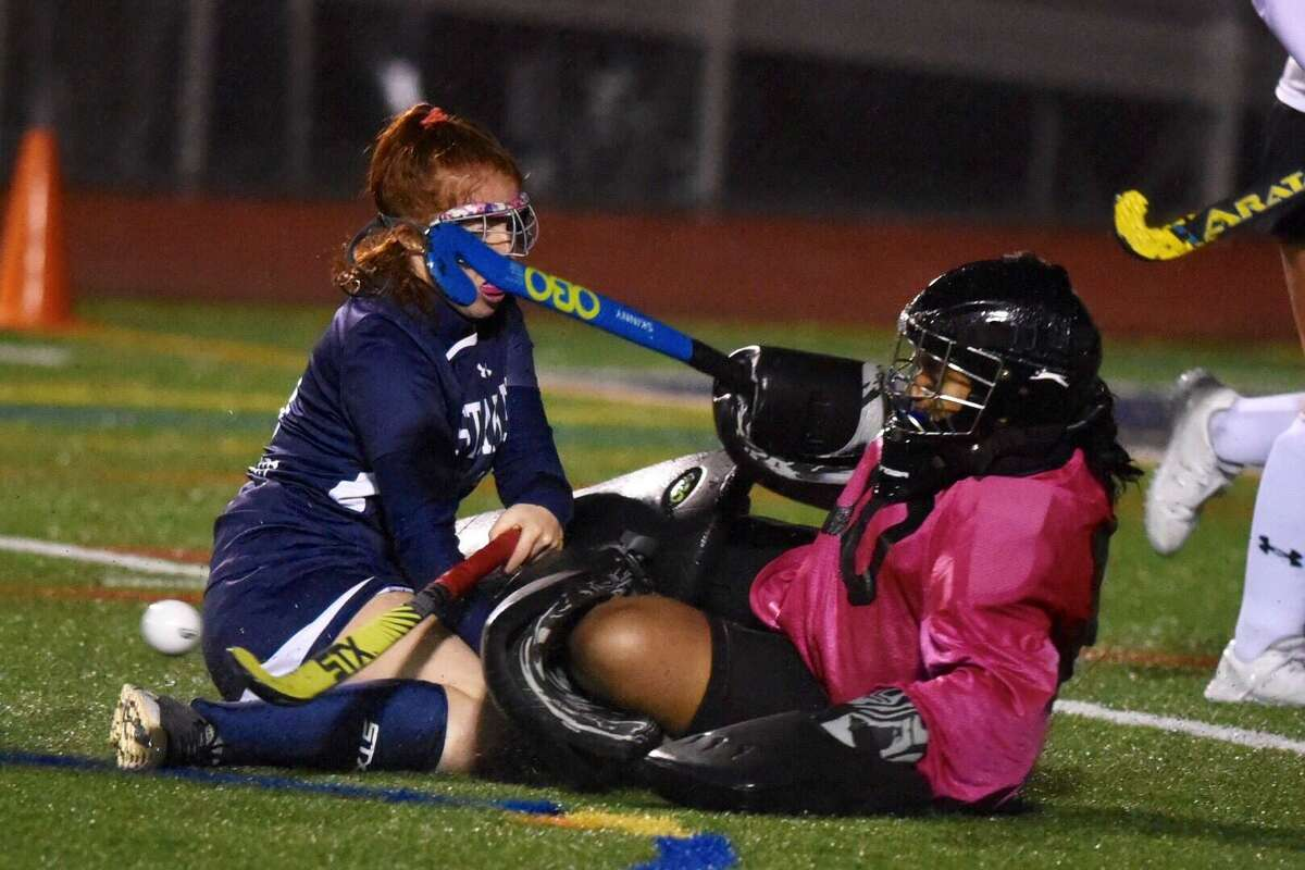 Darien goalie Monisha Akula kicks the ball away while colliding with Staples' Ella Bloomingdale (9) during the FCIAC field hockey final at Brien McMahon on Thursday, Nov. 7, 2019. The game ended in a 0-0 tie after two overtimes, and the teams were declared co-champions.