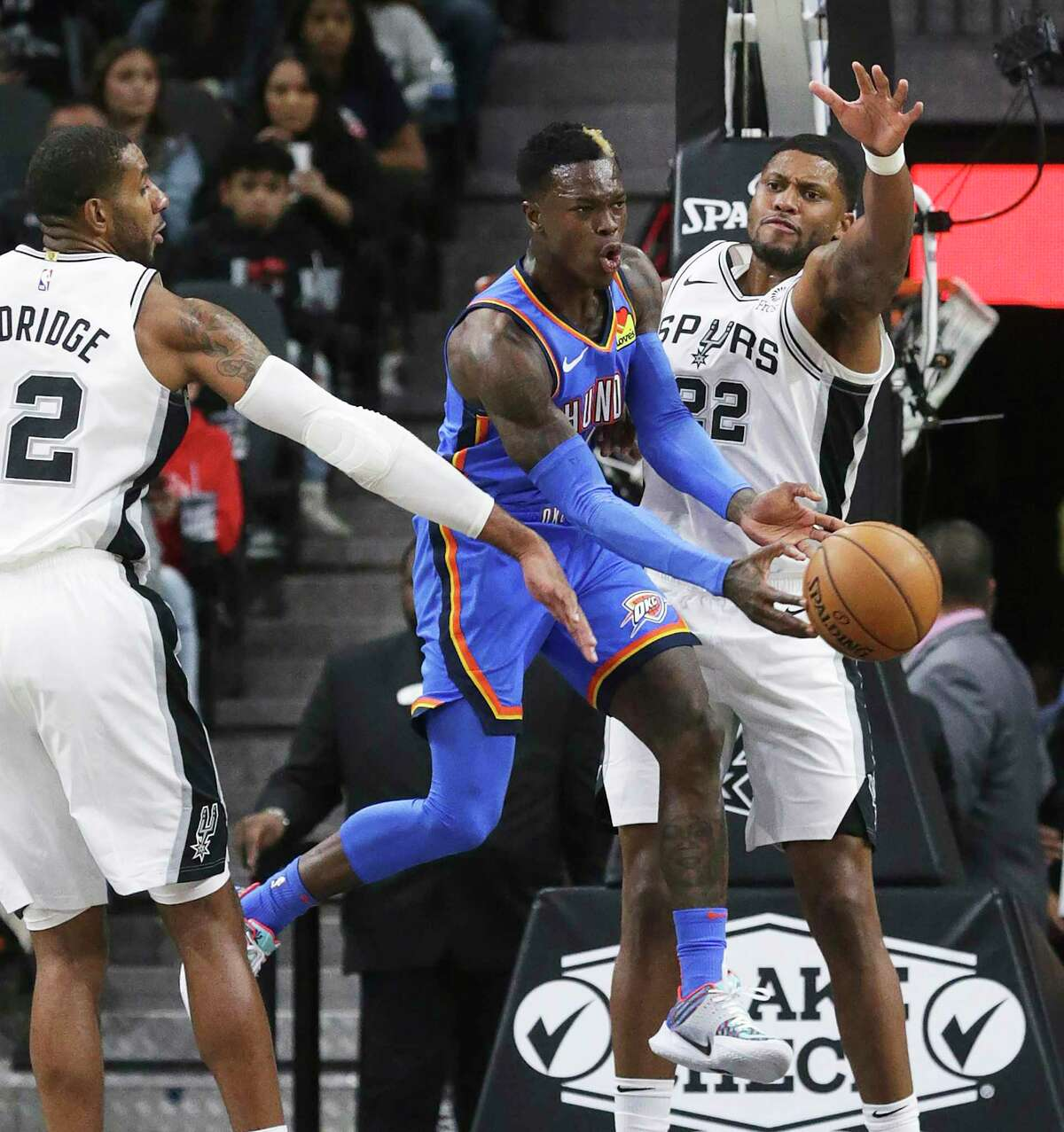 Dennis Schroder passes the ball out from under LaMarcus Aldridge and Rudy Gay as the Spurs hosts the Thunder at the AT&T Center on Nov. 7, 2019.
