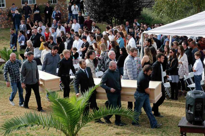 Men carry the remains of Dawna Ray Langford, 43, and her sons Trevor, 11, and Rogan, 2, who were killed by drug cartel gunmen, before they are buried at a family cemetery in La Mora, Sonora state, Mexico, Thursday, Nov. 7, 2019. Three women and six of their children, all members of the extended LeBaron family, died when they were gunned down in an attack while traveling along Mexico's Chihuahua and Sonora state border on Monday. (AP Photo/Marco Ugarte)