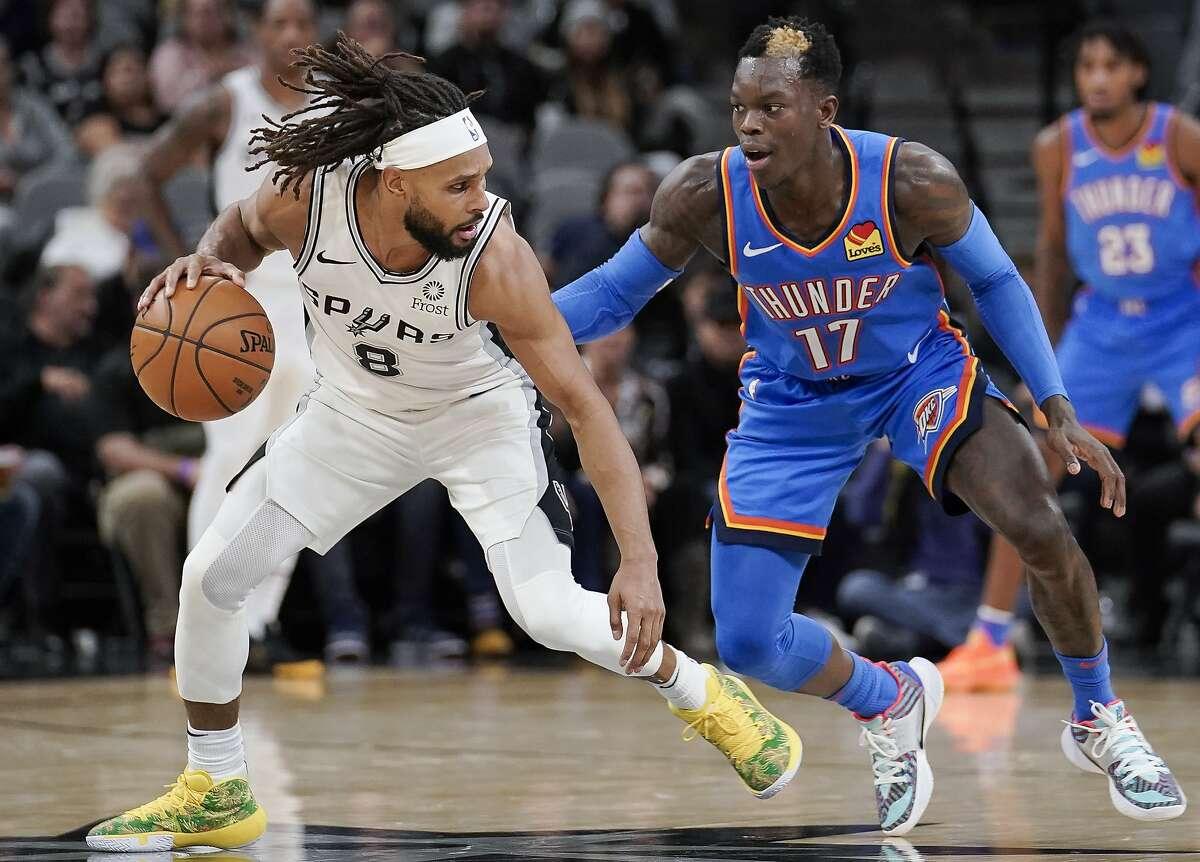 San Antonio Spurs' Patty Mills (8) evades Oklahoma City Thunder's Dennis Schroder during the first half of an NBA basketball game, Thursday, Nov. 7, 2019, in San Antonio. (AP Photo/Darren Abate)