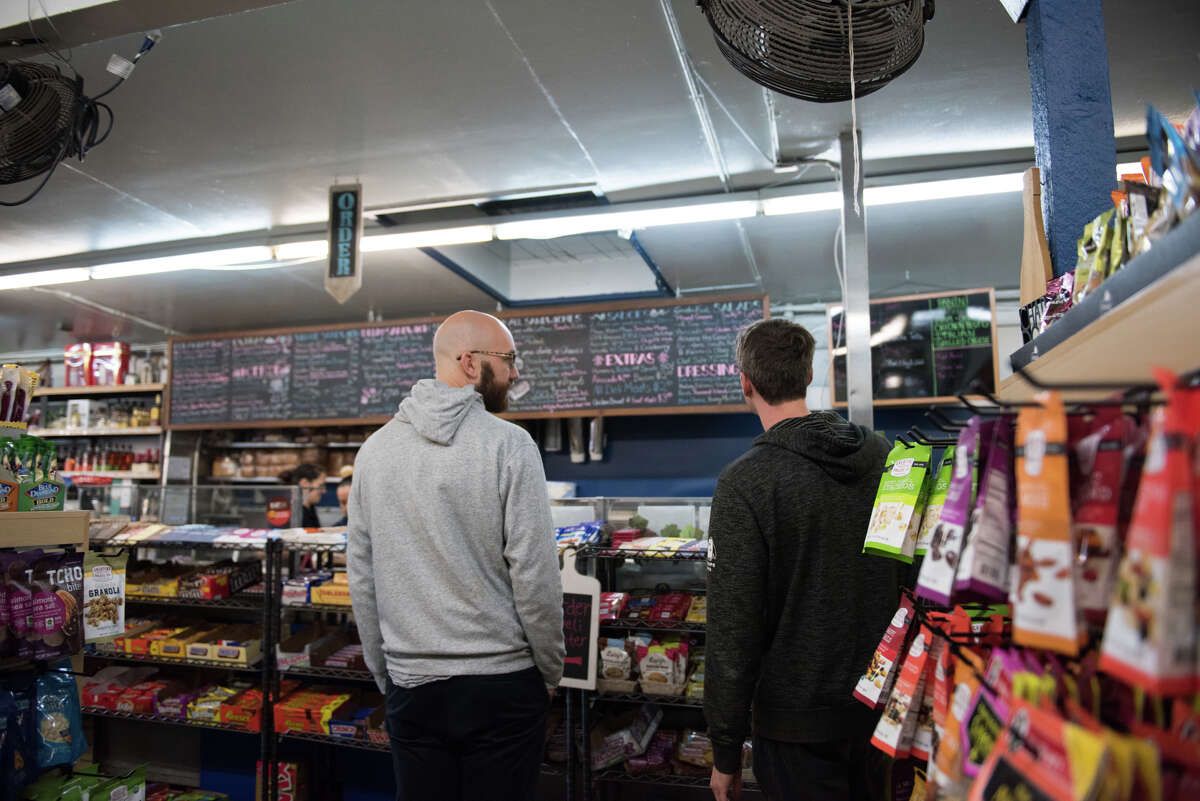 Customers discuss the ample options on the menu board before placing their order.