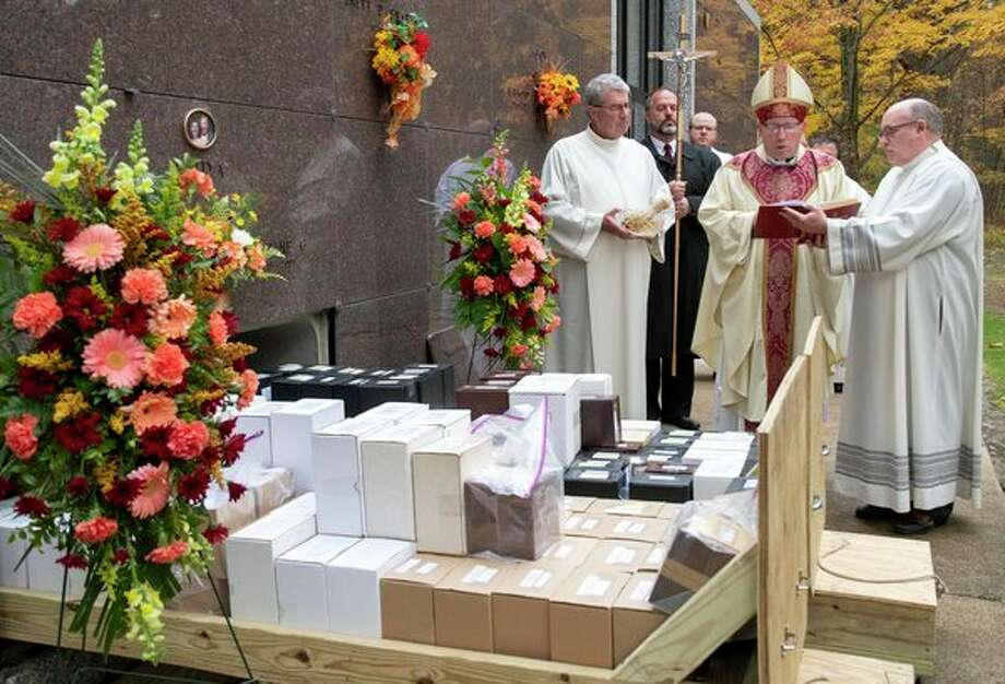 Bishop Robert Gruss of the Diocese of Saginaw leads a sceremony Saturday at Calvary Cemetery in Kawkawlin to inter the unclaimed cremated remains of 175 individuals. (Photo provided)