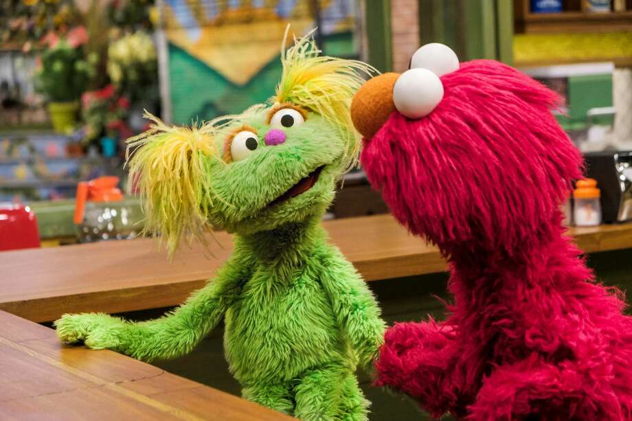 Sesame Street Muppets Karli (pictured left) and Elmo chat on he show. Karli is a 6-year-old Muppet who is living with her mother's addiction. The new character shines light on how children are affected by addiction in their families. Photo: Photo By Flynn Larsen For Sesame