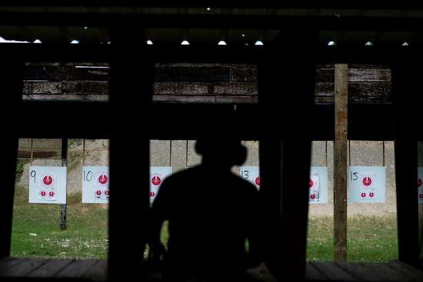 A man loads his gun before shooting at targets in Cypress, Texas.