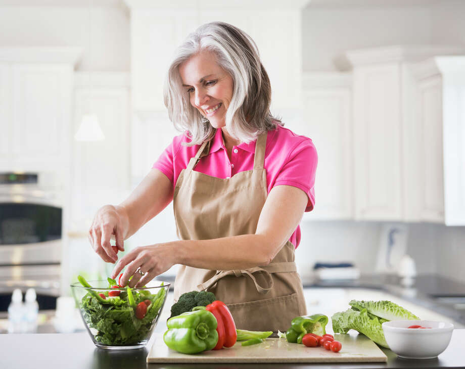 A woman would rather cook at home then go out with friends. Photo: Mike Kemp/Getty Images/Tetra Images RF