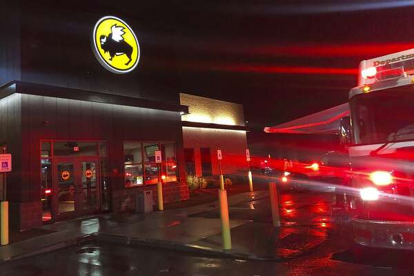 Emergency crews at the Buffalo Wild Wings restaurant in Burlington, Mass. Thursday night, Nov. 7, 2019. Massachusetts authorities say an employee of the restaurant has died and eight others have been hospitalized following a chemical mixture at the restaurant. WHDH-TV reports officials responded Thursday night to reports of a chemical reaction in the kitchen area of the Burlington restaurant where they found a male employee suffering from nausea. (John Guilfoil via AP)