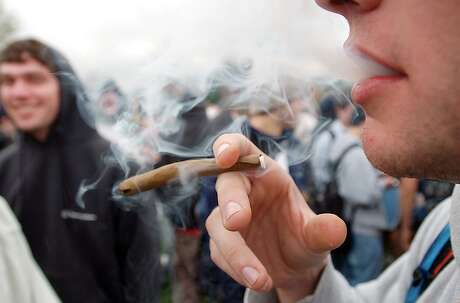 """HOLD FOR MALCOLM RITTER STORY -- FILE - In an April 20, 2005 file photo, a University of Colorado freshman, who did not want to be identified, joins a crowd smoking marijuana during a """"420"""" gathering at Farrand Field at the University of Colorado in Boulder, Colo. People who started using marijuana persistently before age 18 risk losing some of their IQ by the time they're 38, a long-running study says. In contrast, even long-term chronic users who started after age 18 showed no such effect, suggesting the drug holds some particular toxicity for the developing brain. (AP Photo/Longmont Daily Times-Call, Richard M. Hackett, File) MANDATORY CREDIT, MAGS OUT, NO SALES"""