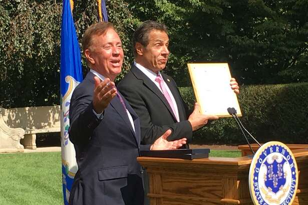 Connecticut Gov. Ned Lamont, left, and New York Gov. Andrew Cuomo share a laugh after Lamont gave Cuomo a mounted Connecticut fishing license at the governor's mansion in Hartford, Sept. 25, 2019.