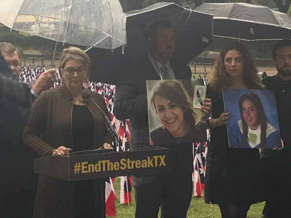 Texas Transportation Commission member Laura Ryan stands with relatives of people killed in roadway crashes outside Houston City Hall at an event Nov. 7, 2019, marking the 19th anniversary of the last day without a road fatality in Texas. Officials staked 3,647 Texas flags, one for each of the people killed on state roadways in 2018, around the Hermann Square Park fountain.