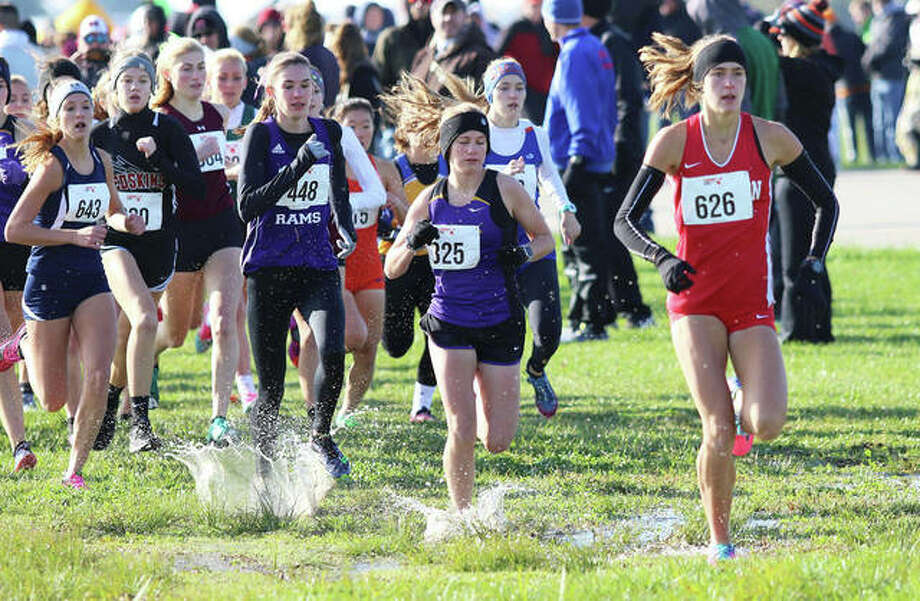 Staunton junior Lydia Roller (right) leads runners through standing water in the first quarter-mile of the St. Anthony Class 1A Sectional cross country meet last Saturday in Effingham. Roller won the race and takes aim at becoming a three-time all-stater Saturday in the state meet at Detweiller Park in Peoria. Photo: Greg Shashack / The Telegraph