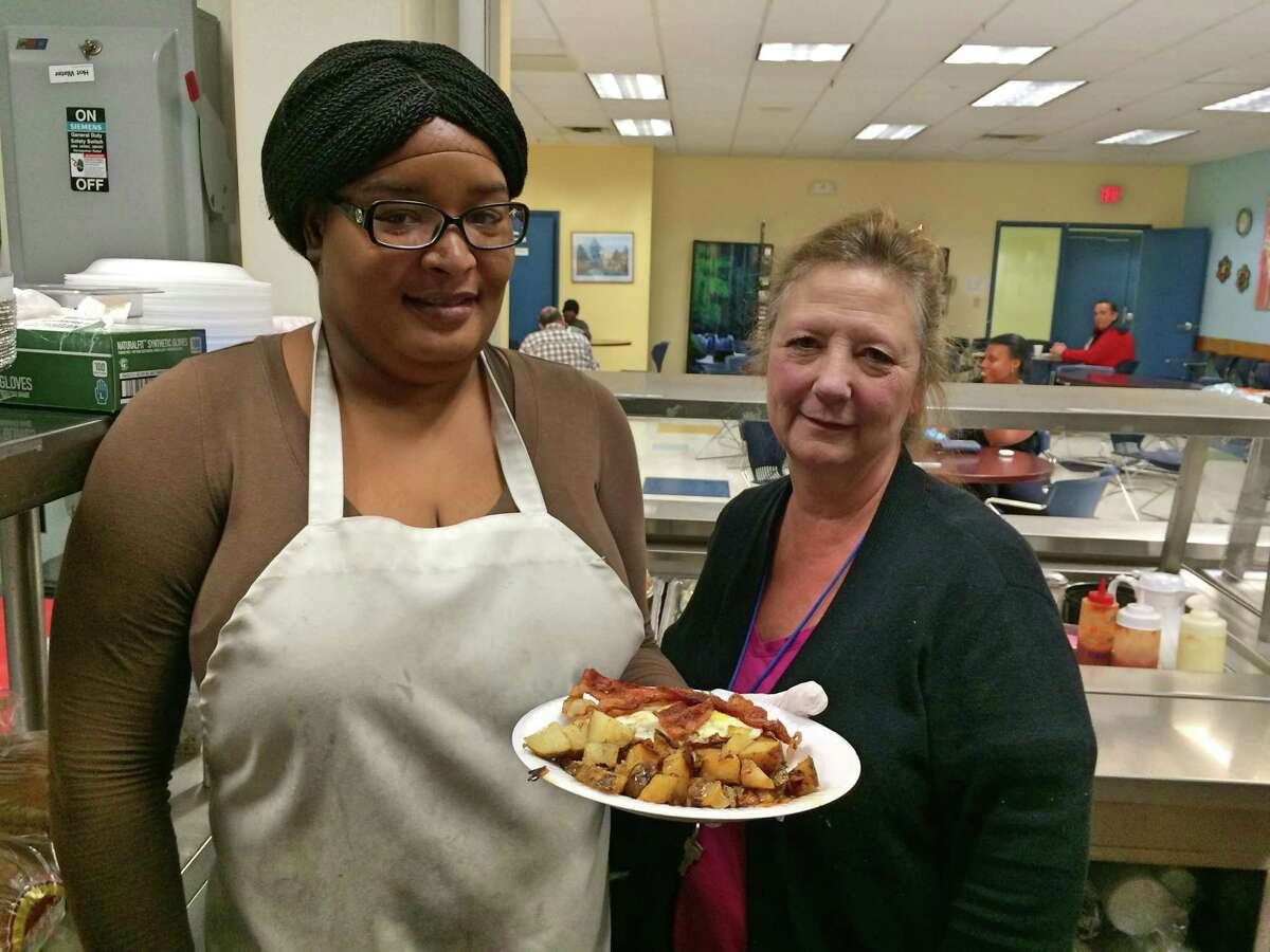 Kabrena Robinson and Soups and Such manager Ann Marie Kenney show off a pancakes, eggs and bacon breakfast that Robinson prepared.