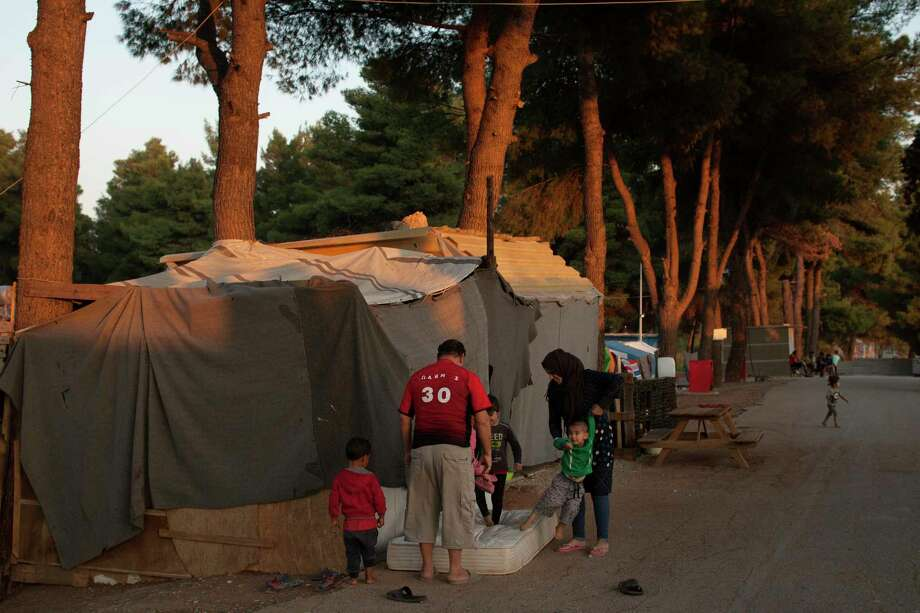 At a refugee camp north of Athens, families seeking asylum live in makeshift housing, with tarps thrown over plywood. Photo: Photo For The Washington Post By Myrto Papadopoulos / Myrto Papadopoulos