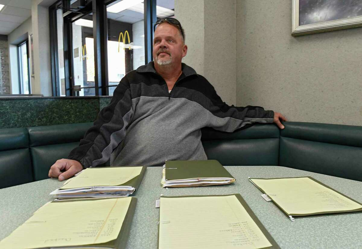 Sean Quinlan, an advocate for tracking sex offenders' residences near schools, is seen with folders and files in front of him on Thursday, Oct. 24, 2019 in Albany, N.Y. (Lori Van Buren/Times Union)