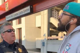 A screenshot from the viral video shows the BART officer holding Steve Foster's backpack as he waits for backup.