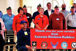 Fifteen veterans and two spouses of veterans gather for a photo after being honored at a local Extreme Business Builders' meeting on Thursday morning.
