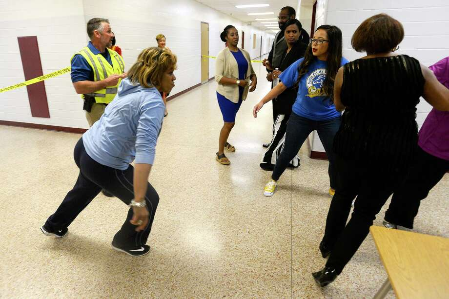 Participants scramble for an exit after hearing gunfire during an active shooter training session at Smith Middle School on Wednesday evening. Beaumont ISD and Beaumont Police Department provided the training to school administrators.  Photo taken Wednesday 2/28/18 Ryan Pelham/The Enterprise Photo: Ryan Pelham / Ryan Pelham/The Enterprise / ©2017 The Beaumont Enterprise/Ryan Pelham