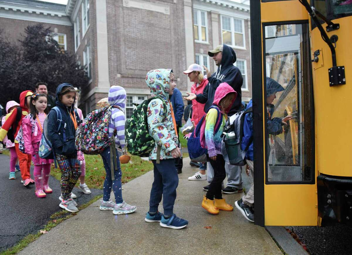 First-graders board a bus bound for Old Greenwich School on students' first day back at Cos Cob School in the Cos Cob section of Greenwich, Conn. Monday, Oct. 15, 2018.