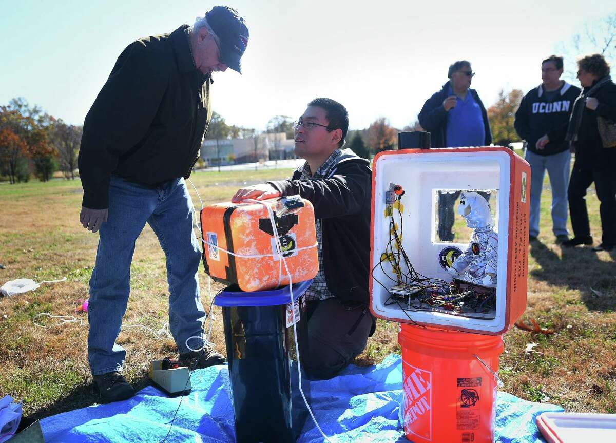 Retired Norden Systems engineer and mentor Larry Reid, left, of Shelton, and recent University of Bridgeport graduate Sam Zhang prepare for the test flight of a high altitude balloon from The Discovery Museum in Bridgeport recently. The payload included a 3D printed animatronic monkey.
