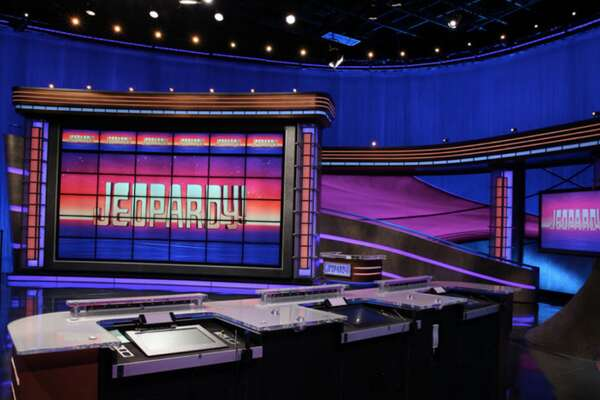 """Can you answer these real Jeopardy questions about TV shows? Created by Merv Griffin, """"Jeopardy!"""" first hit the airwaves in 1964 to become the second highest-rated daytime game show of its time. In 1975, scheduling changes resulted in a ratings drop and the show was unceremoniously canceled. On the heels of some short-lived revivals, a daily syndicated version debuted in 1984. Serving as host was a poised and even-tempered man by the name of Alex Trebek. It's this version that today's audiences still know and love. For those who are (miraculously) unaware, """"Jeopardy!"""" distinguishes itself by way of a rather unconventional trivia method. Specifically, three contestants are presented with the answer to a question, and then tasked with providing the question that's just been answered. The first contestant to guess the proper question receives the associated cash value, and then chooses the next answer. Mixing things up are Daily Doubles, where the contestant can place a wager on the answer and question at hand. The action culminates with Final Jeopardy, in which each contestant must once again bet on him or herself before answering the question, or should one say questioning the answer? As one can probably guess, there's been no shortage of hot streaks over the course of the show's history. Contestant James Holzhauer recently had a record-breaking streak in June 2019 with 32 consecutive wins. Holzhauer's comprehensive trivia knowledgesparked a healthy ratings boost. Of course, even if the show were to end tomorrow, it would leave a truly iconic legacy. Indeed, the theme song and """"SNL"""" parodies alone are already the stuff of television history. Part of the fun of watching """"Jeopardy!"""" is playing along at home. Now, Stacker puts those homegrown skills to the test. Culling from the """"Jeopardy!"""" archives-actual questions and answers from previous episodes-Stacker provides a """"clue"""" about TV shows and then presents the answer in the form of a question. Can you answer these rea"""
