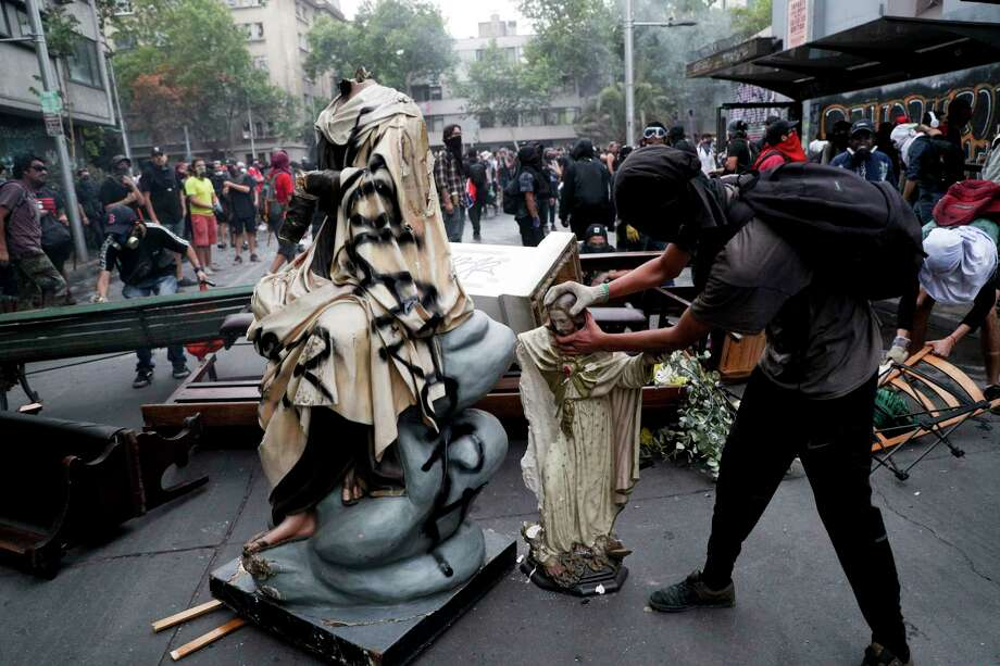 An anti-government protester beheads a statue of Jesus Christ that was taken from a church to be added to a barricade, in Santiago, Chile, Friday, Nov. 8, 2019.  Chile's president on Thursday announced measures to increase security and toughen sanctions for vandalism following three weeks of protests that have left at least 20 dead. Photo: Esteban Felix, AP / Copyright 2019 The Associated Press. All rights reserved