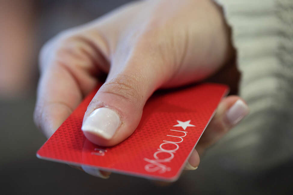FILE - In this Aug. 11, 2019, file photo a woman holds a Macy's card in New Orleans. Signups for retailer credit cards soar during the holidays. (AP Photo/Jenny Kane, File)