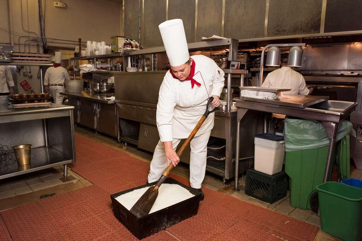 Caitlin Elliott uses a miniature shovel to loosen the grains of a salt-filled bin hiding a 17-pound slab of prime rib.