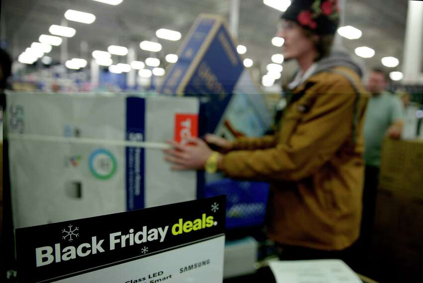 FILE - In this Nov. 22, 2018, file photo people wait in line to buy televisions as they shop during an early Black Friday sale at a Best Buy store on Thanksgiving Day in Overland Park, Kan. Black Friday is Nov. 29, 2019, but it might as well be the whole month of November. (AP Photo/Charlie Riedel, File)