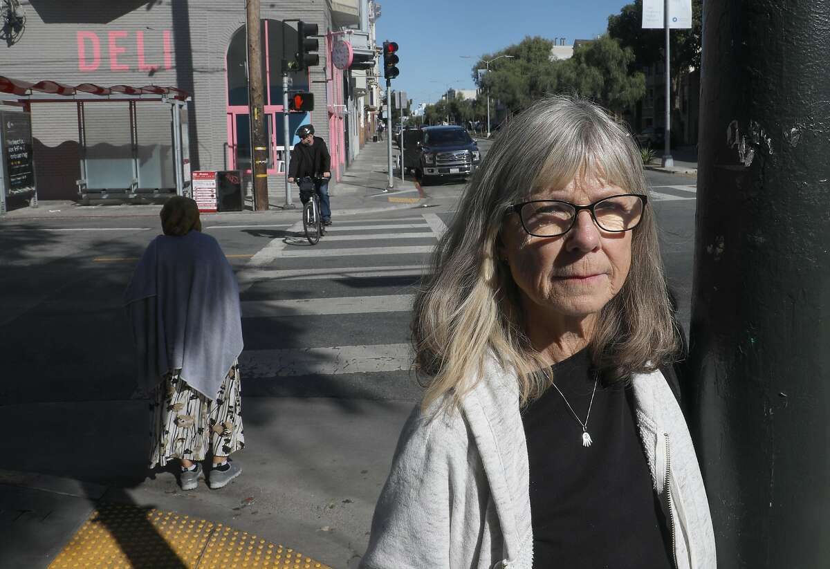Nancy Harrison-Noonan who was struck by a car just behind where cyclist is crossing at left, stands on 18th at Guerrero streets on Thursday, Oct. 10, 2019, in San Francisco, Calif. The driver was at fault, but the SFPD didn't even give him a ticket.