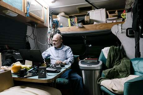 Bill Boutin looks at his laptop inside the RV that he and his wife Kaylynn Reeb live in after power was restored at the Cloverdale Citrous Fairgrounds evacuation center in Cloverdale, California, on Wednesday, Oct. 30, 2019.  Bill and Kaylynn lost their home to the Pocket Fire in Geyserville in 2017, and after living in their RV for the last few years, they recently had to evacuate under threat of the Kincade Fire