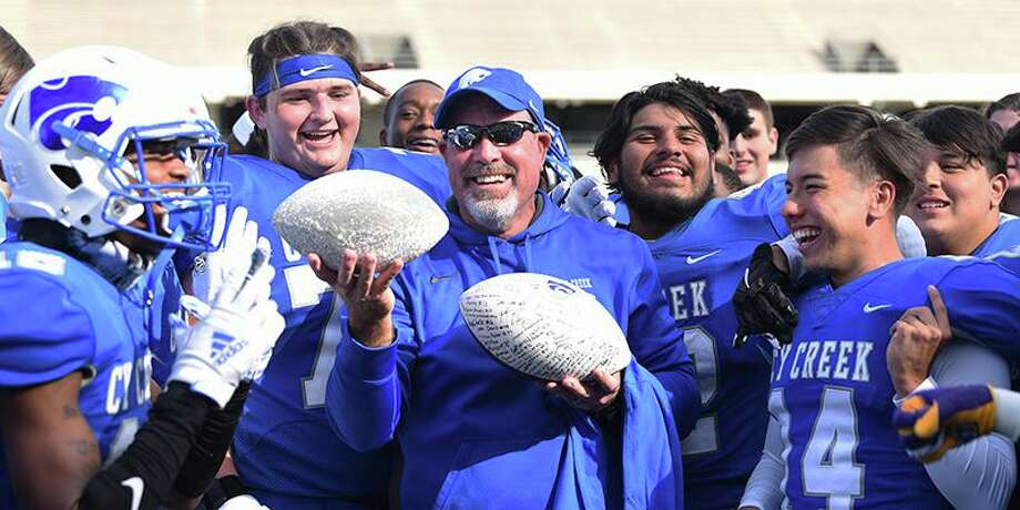 Cy Creek head football coach Greg McCaig celebrates his 100th career win with two game balls after the Cougars defeated Memorial 31-6 on Nov. 2 at Pridgeon Stadium. Photo: CFISD