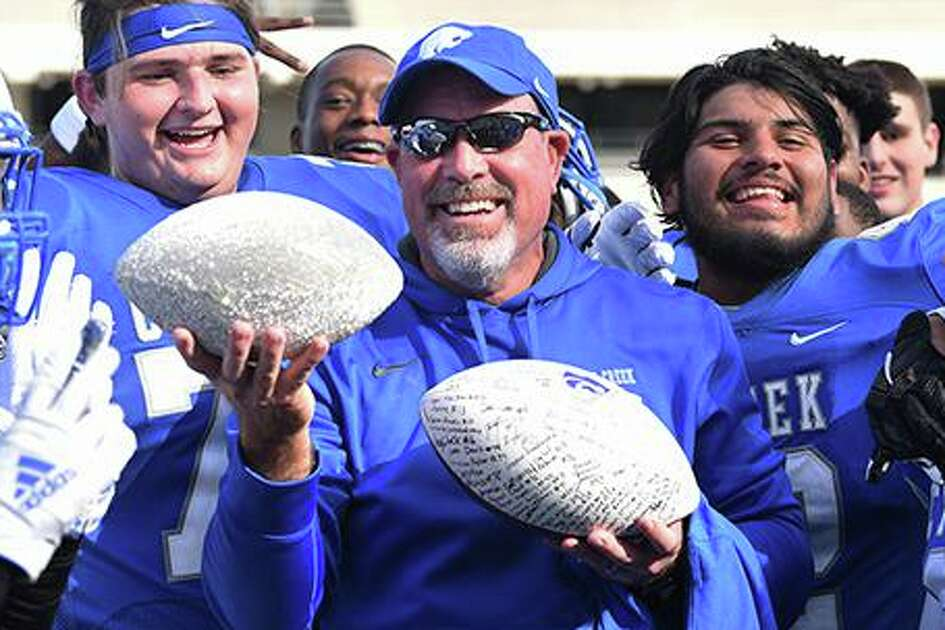 Cy Creek head football coach Greg McCaig celebrates his 100th career win with two game balls after the Cougars defeated Memorial 31-6 on Nov. 2 at Pridgeon Stadium.