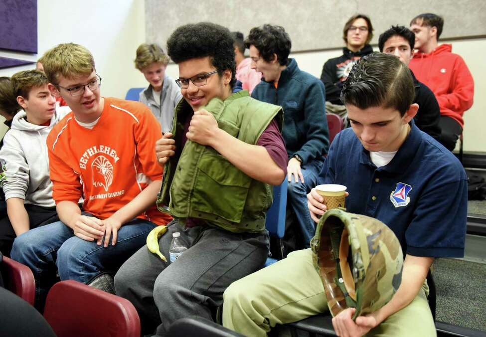 Bethlehem High School students; Anders Baum, left, Daniel Myers and Camden Gorman, right, try on some Vietnam War era combat gear from Henry Neuberger, a Vietnam veteran who served two tours as a Marine Corps radio operator, on Friday Nov. 8, 2019, in Bethlehem, N.Y. (Will Waldron/Times Union)