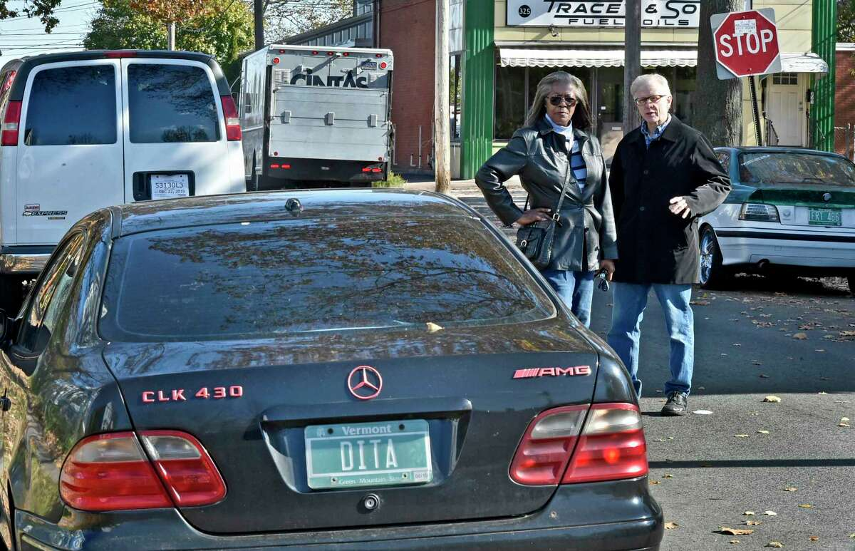 New Haven residents Angela Hatley of Greenwich Avenue, left, and Christopher Schaefer of Second Avenue have issues with a tenant on First Street who has several vehicles with out-of-state plates that take up many of the parking spaces on between Howard and Greenwich avenues. The vehicles around Hatley and Schaefer are three of the cars that concern them: A Mercedes-Benz with Vermont license plates, left; a Chevrolet van with Texas temporary license plates, left, rear; and a BMW with Vermont plates, right.