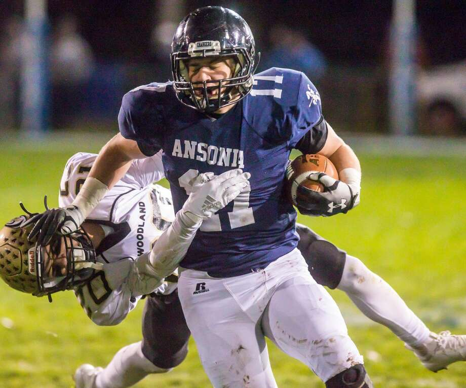 (John Vanacore/For Hearst Connecticut Media) Ansonia running back Tyler Cafaro battles to get past Woodland defender James Champagne during the Charger's 260-20 win over the Hawks Friday night in Ansonia. Photo: John Vanacore, John Vanacore/For Hearst Connecticut Media