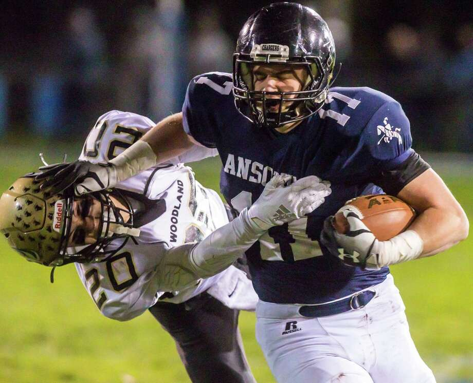 (John Vanacore/For Hearst Connecticut Media) Ansonia running back Tyler Cafaro battles to get past Woodland defender James Champagne during the Charger's 260-20 win over the Hawks Friday night in Ansonia. Photo: John Vanacore / For Hearst Connecticut Media / Stamford Advocate Freelance