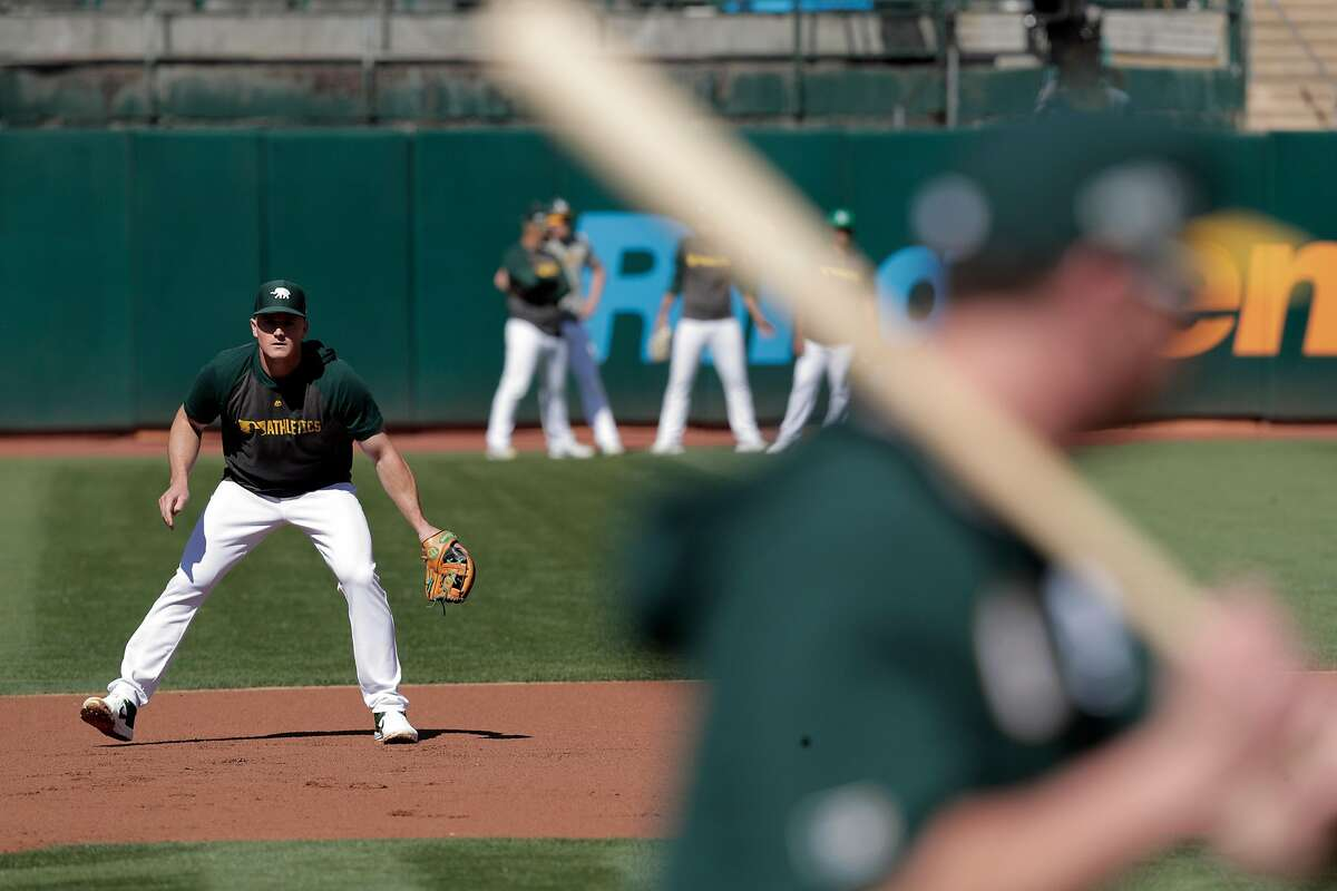 Matt Chapman (26) takes grounders as A's players warm up before the Oakland Athletics played the Tampa Bay Rays at the Oakland Coliseum in the Wild Card playoff game in Oakland, Calif., on Wednesday, October 2, 2019.